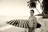INDONESIA, Mentawai Islands, Kandui Resort, portrait of young man holding surfboard on beach (B&W)