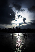 Teenage girls take photographs of each other on Chowpatty beach in Mumbai.