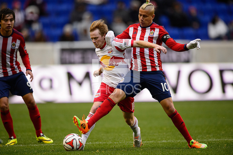 Adolfo Bautista (10) of Chivas USA and Dax McCarty (11) of the New York Red Bulls battle for the ball. The New York Red Bulls and Chivas USA played to a 1-1 tie during a Major League Soccer (MLS) match at Red Bull Arena in Harrison, NJ, on March 30, 2014.