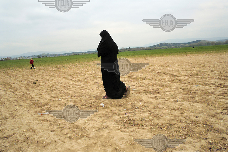 A refugee woman, dressed in a chador, walks accross a farmer's field towards the makeshift refugee camp at Idomeni. Around 14,000 people were stranded in the camp which the authorities have since closed and distributed the occupants among several official camps around the country.