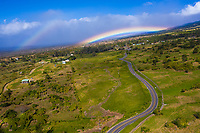 Rainbows over a winding road through Ulupalakua Ranch, Maui.
