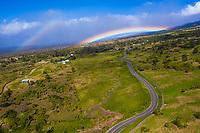 Rainbows over a winding road through Ulupalakua Ranch, Maui.