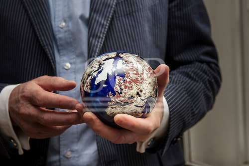 London, England. Businessman holding a globe of the Earth made of semi-precious stones.
