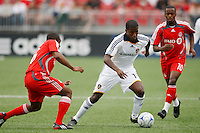 Los Angeles Galaxy forward Edson Buddle (14) goes between Toronto FC defender Marvell Wynne (16) and midfielder Rohan Ricketts (10). Toronto FC defeated the Los Angeles Galaxy 2-0 during a Major League Soccer match at BMO Field in Toronto, Ontario, Canada, on May 31, 2008.