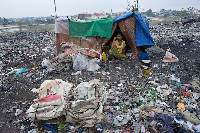 RUBBISH DUMP RECYCLING. South East Asia, Cambodia, Phnom Penh. Smokey Mountain, Steung Mean Chey, is Phnom Penh's municipal rubbish dump. Thousands work there, some 600 minors and 2000 adults, recycling the city's rubbish, dumped there by garbage trucks every day. The dump is notorious as many very young children work there. People eat and sleep overnight in the rubbish and fumes, under plastic tarpaulins or in the open air. They work 24 hours a day, like miners, with headlamps at night, collecting plastic, metals, wood, cloth & paper, which they sort and clean, weigh and sell, to be carried away for recycling. A day's work typically brings less than a dollar per person. One and a half to two dollars per day per family. The overpowering, acrid odour of grey smokey fumes blows across the dump, from which the place gets its name 'Smokey Mountain'. It can be smelt miles away. The shantytowns and squats, the recycling worker's homes butt onto or are inside the dump itself. There is no running water, sanitation and many are ill. Children often work with friends or relatives. Religious and ngo's help some children, but this is often resisted by families who need the extra income they generate.///Sitay's mother. Sitay, aged 8 years, is the sole earner for her family. She works with her mother's friends. Her mother is ill and her father dead. They live in a squat inside the rubbish dump, unable to afford rent.