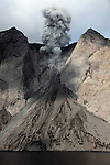 Ash cloud from active crater and debris slope below at Batu Tara Volcano, Komba Island, Indonesia.