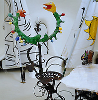 Detail of a sculptural chair made from an old tractor seat and a papier-mache double headed snake with colorful light bulbs