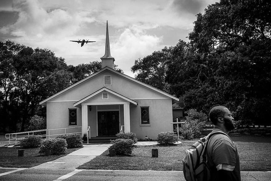 Taking off from Hilton Head Airport, a U.S. Airways plane passes over the St. James Baptist Church, which is located on property where the Gullah Geechee have worshiped since 1886. Airport improvement plans approved by the Beaufort County Council and Town of Hilton Head Island Town Council would extend the runway through the church site. Desperate to preserve their church, the Gullah Geechee are fighting the project.