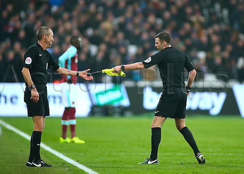 February 11th 2017, London Stadium, London, England, Premier League football, West Ham versus West Bromwich Albion;  Referee Michael Oliver hands Assistant referee Mick McDonough a replacement flag, after his original broke during a throw in signal