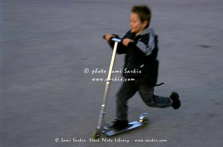 Young boy speeding on a kick scooter.