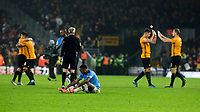 27th December 2019; Molineux Stadium, Wolverhampton, West Midlands, England; English Premier League, Wolverhampton Wanderers versus Manchester City; Raheem Sterling of Manchester City sat on the grass after the final whistle and a 3-2 defeat whilst Wolverhampton Wanderers players celebrate their win - Strictly Editorial Use Only. No use with unauthorized audio, video, data, fixture lists, club/league logos or 'live' services. Online in-match use limited to 120 images, no video emulation. No use in betting, games or single club/league/player publications