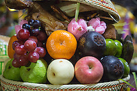 Bali, Indonesia.  Basket of Fruits and Sweets Left as an Offering at Pura Dalem Temple, Dlod Blungbang Village.  The offering is in hope of a good rice harvest.
