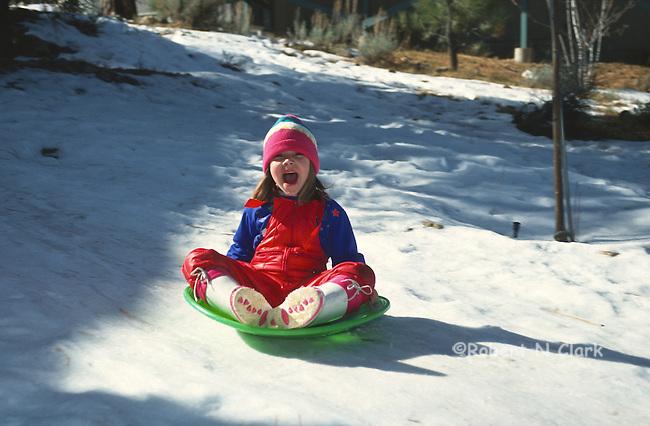 Girl sliding on snow saucer
