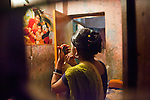 "Faridpur Brothel is the second to largest brothel in Bangladesh. (17 registered brothels in the country) 600+ girls live in a hidden neighboorhood accesible through one of the six alleyways, covered with small ragged curtains mimicking doors. Many girls are under aged - the ""legal"" age being 18. A girls prepares for the evening to come. March 10, 2011. Gabriela Barnuevo"
