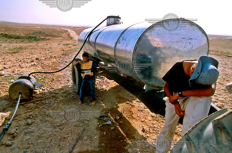 Children from the Bedouin tribe of El-Assam fill a tank with water, drawn illegally from an official water pipeline.  This is the water supply point for the unrecognised Bedouin villages within a radius of 15km radius.
