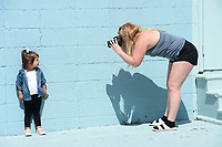 Tonia Hanson (right), owner of Tonia Hanson Photography in Fayetteville, takes a photograph Thursday, May 21, 2020, of Charleston Smolinski, 3, while taking family photographs with Charleston's twin brother, Roman, and mother, Ally Smolinski of Rogers, in front of the Maude Wall at Maude Boutique in Fayetteville. The clothing store invites patrons to use their multicolored back wall for photographs. Visit nwaonline.com/200522Daily/ for today's photo gallery.<br /> (NWA Democrat-Gazette/Andy Shupe)