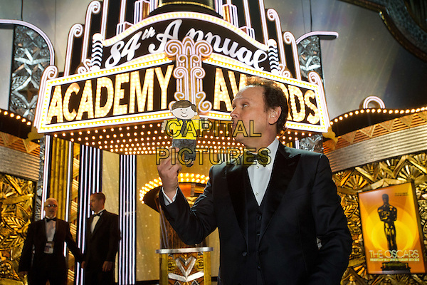 Host Billy Crystal poses onstage following the live ABC Television Network broadcast of the 84th Annual Academy Awards® from the Hollywood and Highland Center, in Hollywood, CA, Sunday, February 26, 2012..*Editorial Use Only*.oscars half length stage black tuxedo  drawing profile .CAP/A.M.P.A.S./NFS.©A.M.P.A.S. Supplied by Capital Pictures.