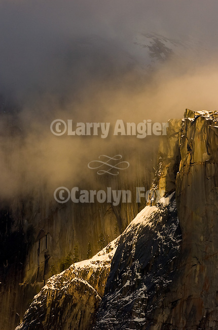 Half Dome with snow obscured by clouds in the late afternoon.