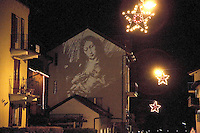 "Switzerland. Canton Tessin. Vira Gambarogno. Video projection on the wall of mary holding in her arms Jesus. Mary, called since medieval times Madonna (My Lady), is known from the New Testament as the mother of Jesus of Nazareth. The New Testament describes her as a young maiden who conceived by the agency of the Holy Spirit whilst she was already the betrothed wife of Joseph of the House of David and awaiting their imminent formal ""Home-taking"" ceremony (the concluding Jewish wedding rite). To many believers the accounts in the canonical ""Birth narratives"" suggest that she had still been a virgin at the time of the child's birth as well as at his conception. Illuminaion at night for the Christmas holiday season. Stars. © 2007 Didier Ruef"