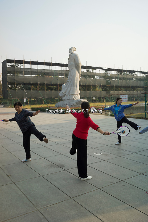 Huanggang, Hebei province, China - Residents perform morning exercise underneath a statue of famous Song dynasty poet and politician Su Dongpo at the Yiai Park, October 2014.