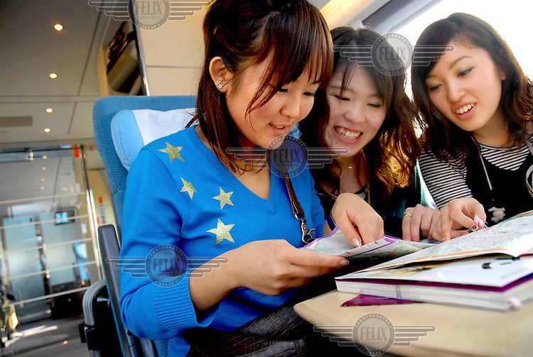 A group of Japanese tourists, travelling on the AVE (Alta Velocidad Espanola) high-speed train, study a map of Barcelona, their next destination after spending a few days in Madrid.