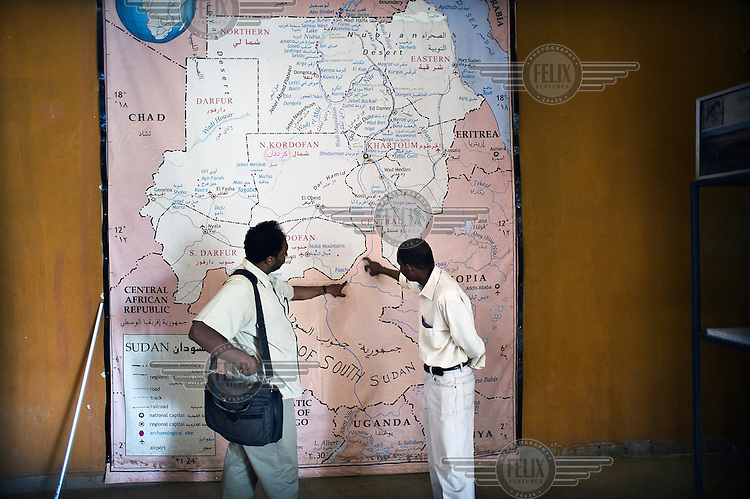 Two Sudanese men standing in front of a map of part of N E Africa, displayed in the lobby of the National Museum, discuss the new shape of their country following the independence of South Sudan.