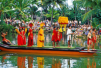 A re-enactment at the Polynesian Cultural Center of a traditional Hawaiian canoe procession with a close-up of one canoe carrying local actors portraying Hawaiian royalty, complete with red and yellow feather costumes and kahili. Tourists line the b
