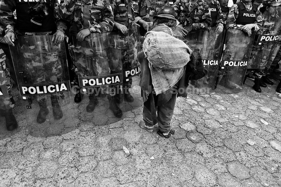 An old barefoot Indian passes through the riot police block during the Inti Raymi (San Juan) festivities in Cotacachi, Ecuador, 29 June 2010. 'La toma de la Plaza' (Taking of the square) is an ancient ritual kept by Andean indigenous communities. From the early morning of the feast day, various groups of San Juan dancers from remote mountain villages dance in a slow trot towards the main square of Cotacachi. Reaching the plaza, Indians start to dance around. They pound in synchronized dance rhythm, shout loudly, whistle and wave whips, showing the strength and aggression. Dancers from either the upper communities (El Topo) or the lower communities (La Calera), joined in respective coalitions, seek to conquer and dominate the square and do not let their rivals enter. If not moderated by the police in time, the high tension between groups always ends up in violent clashes.
