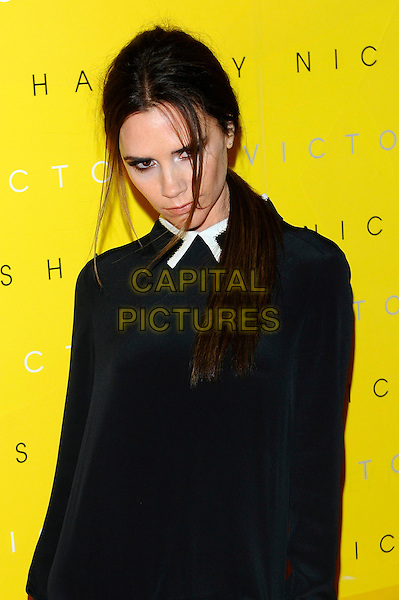Victoria Beckham.attending the unveiling of her 'Victoria by Victoria Beckham' Clothing Line during London Fashion Week, Harvey Nichols, Knightsbridge, London, England, UK, 17th February 2012..LFW half length black top side hair ponytail white trim collar shirt funny moody head down .CAP/CJ.©Chris Joseph/Capital Pictures.