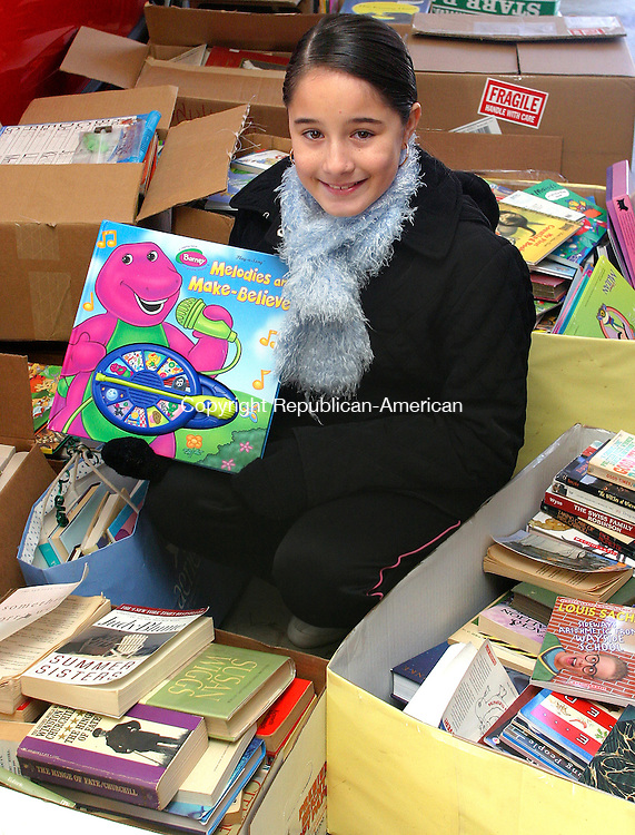 WOLCOTT, CT.-22 JANUARY 2009-012290DA03- Cynthia Dias, 10 of Wolcott helped organized a book collection drive from local elementary schools collecting 1,298 books for Waterbury P.A.L. literary program. Members of the Waterbury Police Activity League were on hand to load the donations on a bus at Dias's home Friday.