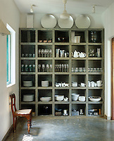 A large grey polished concrete shelving unit dominates one wall of the kitchen