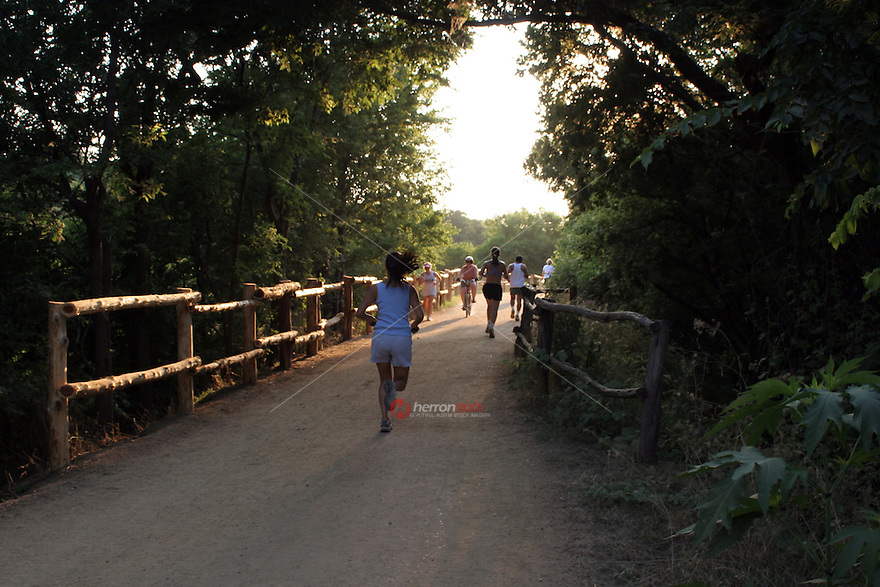 Austin Runners and joggers run and exercise on the Lady Bird Lake Hike & Bike Trail in downtown Austin, Texas