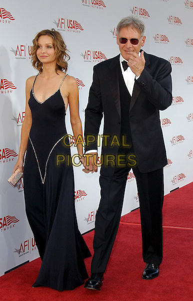 CALISTA FLOCKHART & HARRISON FORD.The 33rd AFI Life Achievement Award: A Tribute to George Lucas held at The Kodak Theatre in Hollywood, California  .June 9th, 2005.full length celebrity couple boyfriend girlfriend tuxedo sunglasses shades black dress holding hands diamante trim.www.capitalpictures.com.sales@capitalpictures.com.Supplied By Capital PIctures