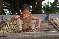 A young girl is brushing her teeth outside her home on the Tonle Sap. Life on and around the Tonle Sap Lake Cambodia
