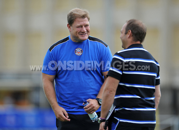 Forwards coach Neal Hatley smiles during the pre-match warm-up. Pre-season friendly match, between Bath Rugby and the Scarlets on August 16, 2014 at the Recreation Ground in Bath, England. Photo by: Patrick Khachfe / Onside Images