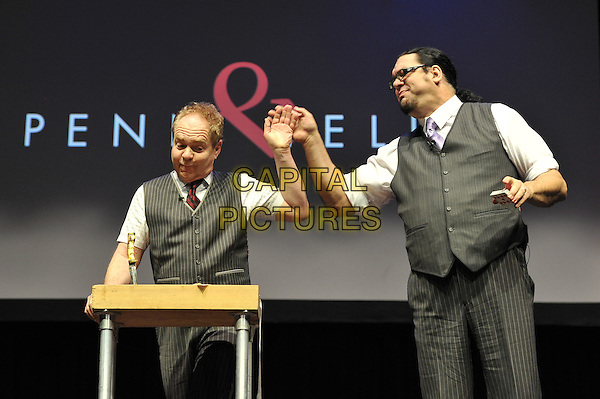 Raymond Joseph Teller & Penn Jillette .Penn and Teller performing 'Conversations with Penn and Teller - 35 Years of Magic and Bulls'%+t', indigo2, Greenwich, London, England. .7th December 2011.bullshit stage concert performing performance half length grey gray waistcoat white shirt profile holding hands table .CAP/MAR.© Martin Harris/Capital Pictures.