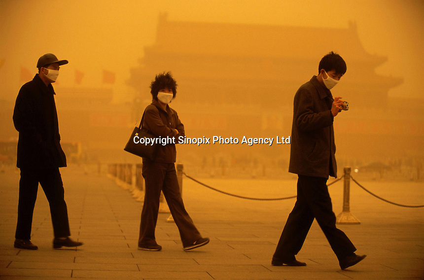 Three tourists wear respirator while walking in the Tananmen Square in Beijing, China. A dust storm strikes Beijing, turning the sky an amber color and reducing visibility to about 1/3 mile. Extensive deforestation and desertification in northern China have fueled the dust storms. Nearly one million tons of Gobi Desert sand blows into Beijing each year..20-MAR-02