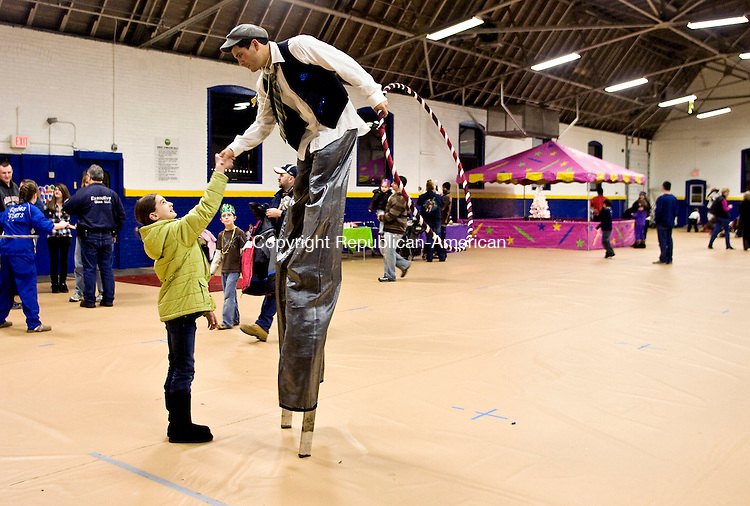 TORRINGTON, CT - 31 DECEMBER 2009 -123109JT04--<br /> Bailee Nardi, 9, of Torrington, shakes hands with Edwin Olvera, also of Torrington, as he stands on stilts at Thursday's Last Night celebration at the Torrington Armory, hosted by the Parks and Recreation department.<br /> Josalee Thrift Republican-American