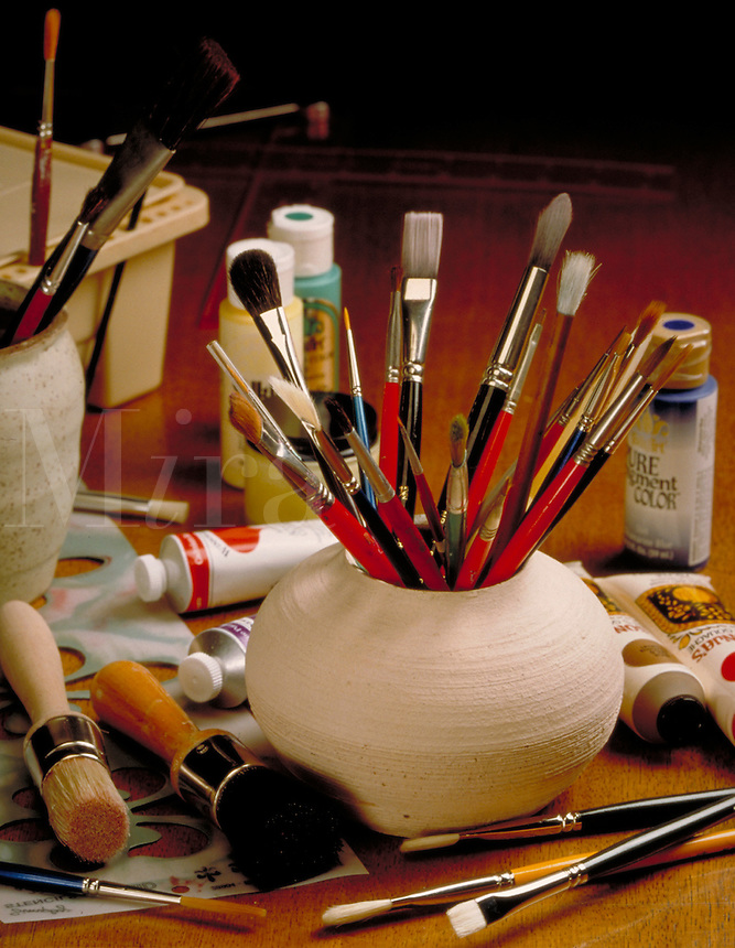 Art brushes in a pot surrounded by paints and other artists tools, art, painting.