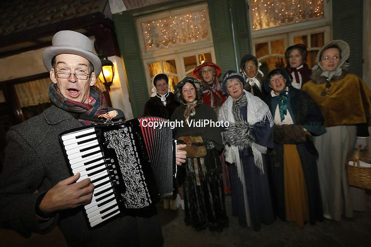 Foto: VidiPhoto<br /> <br /> GARDEREN &ndash; Hoewel Sinterklaas zijn verjaardag nog moet vieren, is het eerste Dickensfeest al een feit. Bij de bekende beeldentuin in Garderen, jaarlijks goed voor 170.000 bezoekers van het grootste zandsculturenfestijn van ons land, ging donderdag de zevendaagse Charles Dickensfair van start. Duizenden bezoekers uit het hele land togen naar de Veluwe om de ongeveer 200 in 19e eeuwse kleding gestoken standhouders en acteurs te bekijken. Het evenement wordt dit jaar voor de negende keer gehouden en trekt ieder jaar meer publiek. Het is bovendien grotendeels overdekt, in nagebouwde straten uit de periode Dickens.