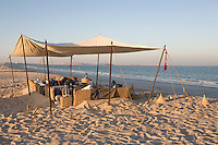 A reception tent set up on the shoreline as the sun sets low over the desert behind it