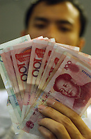A shop keeper shows RMB, Shenzhen, China..