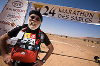 The Marathon des Sables is a 6-day endurance race of 243 km equivalant to 5 1/2 marathons. It plays out in the Sahara Desert, southern Morocco, up and down sand dunes, along dried lakes and riverbeds, past ruins, always under the baking sun. Competitors at the Marathon des Sables expierence mid-day temperatures of up to 120°F. They are running or walking on even rocky, stony ground as well as 15-20% of the distance being in sand dunes. In addition to that, competitors have to carry everything they will need for the duration of the race on their backs in a rucksack. Water is rationed and handed out at each checkpoint. It is the hardest footrace on earth...Der Marathon des Sables in der marrokanischen Sahara gilt als der wohl härteste und bekannteste Wüstelauf der Welt. Ein Ultralauf über 243 Kilometer, der in 6 Etappen zwischen 27 und 82 Kilometer in 7 Tagen gelaufen wird. Die längste Etappe geht bis spät in die Nacht hinein. Die Läufer tragen ihre Ausrüstung und Verpflegung für das ganze Rennen im Rucksack. Lediglich Wasser (9 Liter pro Tag) gibt es an den Checkpoints. Die Teilnehmer laufen über Sanddünen, steiniges Gelände und steile Berganstiege. Die Hitze kann bis zu 50 Grad Celsius betragen.