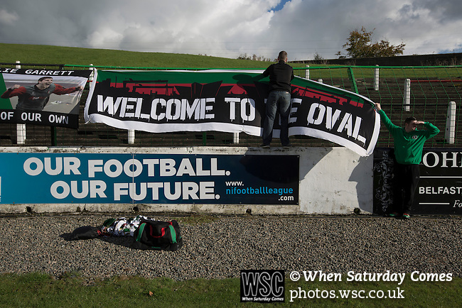 Glentoran 2 Cliftonville 1, 22/10/2016. The Oval, NIFL Premiership. Two men putting up a home team's banner at The Oval, Belfast before Glentoran hosted city-rivals Cliftonville in an NIFL Premiership match. Glentoran, formed in 1892, have been based at The Oval since their formation and are historically one of Northern Ireland's 'big two' football clubs. They had an unprecendentally bad start to the 2016-17 league campaign, but came from behind to win this fixture 2-1, watched by a crowd of 1872. Photo by Colin McPherson.