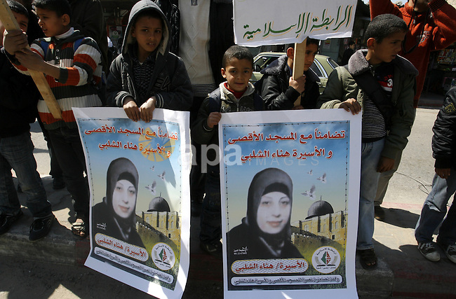 Palestinians demonstrate in solidarity with Hana'a Shalabi during a protest in Rafah, southern Gaza Strip on March 7, 2012. Shalabi, released by Israel in a prisoner swap last year but re-arrested earlier this month and held without charge, is on a hunger strike to protest her treatment, officials said. The Arabic writing on the sign reads ''Down with administrative detentions'. Photo by Abed Rahim Khatib