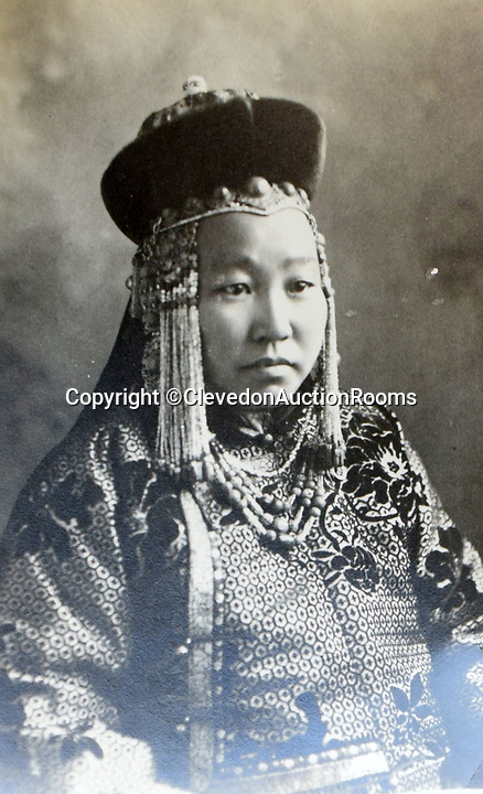 BNPS.co.uk (01202 558833)<br /> Pic: ClevedonAuctionRooms/BNPS<br /> <br /> The wife of a local ruler.<br /> <br /> Rev Francis John Griffith travelled as a Missionary aroud Outer Mongolia in the 1920's.<br /> <br /> A fascinating collection of early 20th century photos of Mongolia and China which were taken by a British vicar doing missionary work have been unearthed after 97 years.<br /> <br /> Through his famine relief work Reverend Francis John Griffith was able to get a remarkable insight into the lives of the native population and their nomadic existence.<br /> <br /> His encounters were captured using a handheld camera that he carried with him at all times.<br /> <br /> In one image a family goes about its business outside the hut that is their home, while another image is of a man riding a camel which was the typical method of transport.<br /> <br /> Revd Griffith was able to get native elders to sit for him in portraits and there are intimate snaps of women and children wearing elaborate native headdresses.<br /> <br /> As well as the people, Revd Griffith took an interest in the surroundings and photographed temples and prominent buildings in addition to the vast, desert landscape.