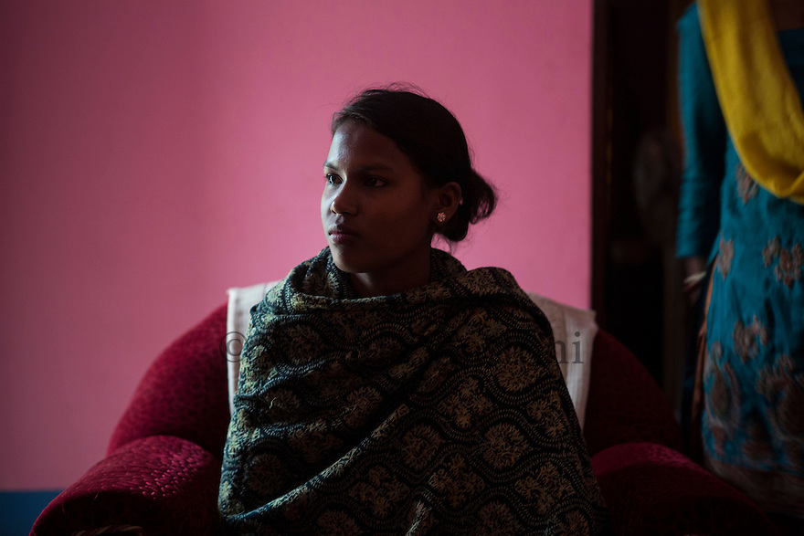India – West Bengal: Sima Lohar, 20, portrayed  in a friend's house at Kathalguri Tea Estate, in the Dooars region. Given the prolonged closure of the tea estate until 2013, Lohar went to work as a domestic worker for almost three years in the cities of Chandigarh and Delhi. Duped and repeatedly raped by her agent who stole all her money, Lohar managed to come back to Kathalguri with the help of her family. She is now working for a local NGO which provides assistance to victims of trafficking.