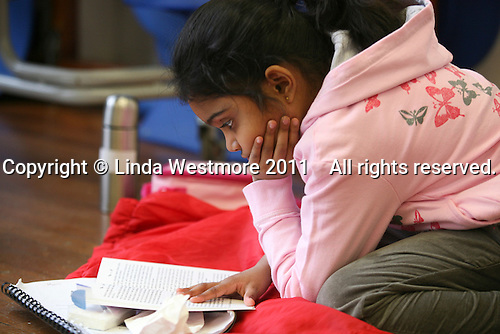 """Reading a book during a break.  Drama group for 8-13s run by Yvonne Arnaud Theatre, rehearsing a production of """"Alice"""" in a school hall, Guildford, Surrey."""