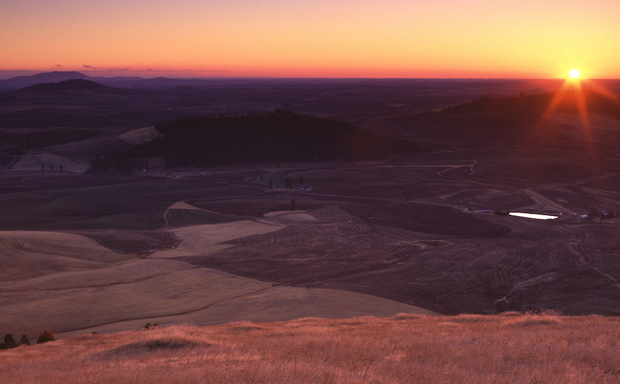 The sun shines on the horizon as it sets over the Palouse seen from Mary Minerva McCroskey State Park in Idaho.