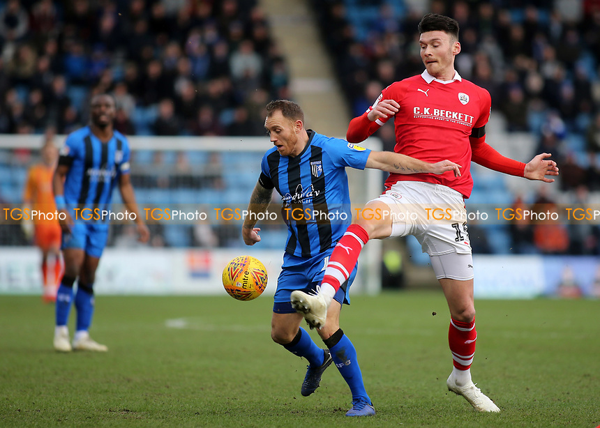 Gillingham's Barry Fuller shields the ball from Kieffer Moore of Barnsley during Gillingham vs Barnsley, Sky Bet EFL League 1 Football at The Medway Priestfield Stadium on 9th February 2019